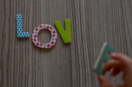 Child is Writing Word Love From Colourful Toy Letters