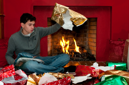 124716731-young-man-unwrapping-presents-gettyimages