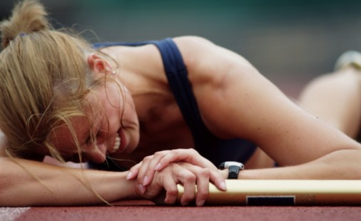 woman lying on athletic track in pain