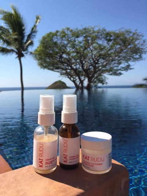 Kat Rudu Beauty Collection -- image of bottles against a backdrop of sky, pool, and trees