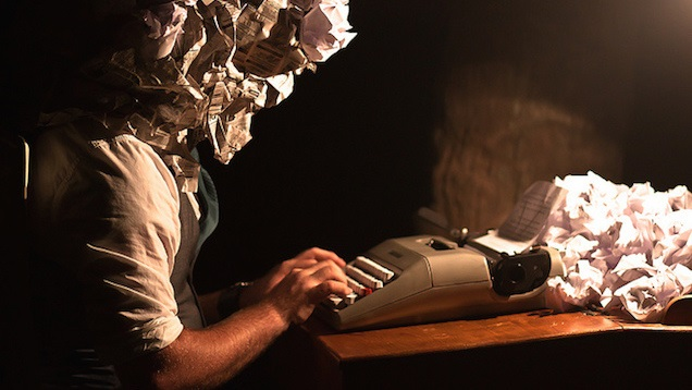 man with head made of crumpled paper typing at typewriter