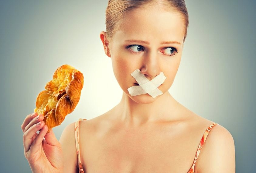 woman holding  fried food with duct tape over her lips