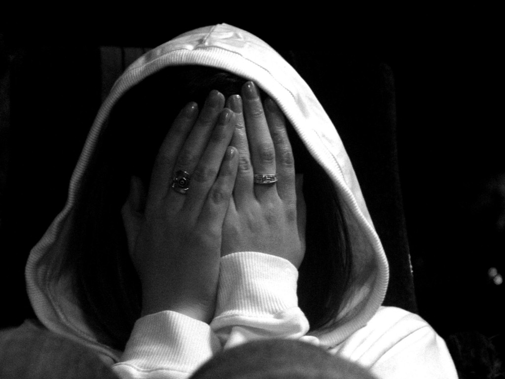 woman covering face with hands in anguish
