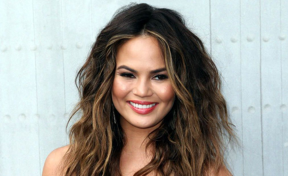 chrissy teigen posing in front of gray background smiling