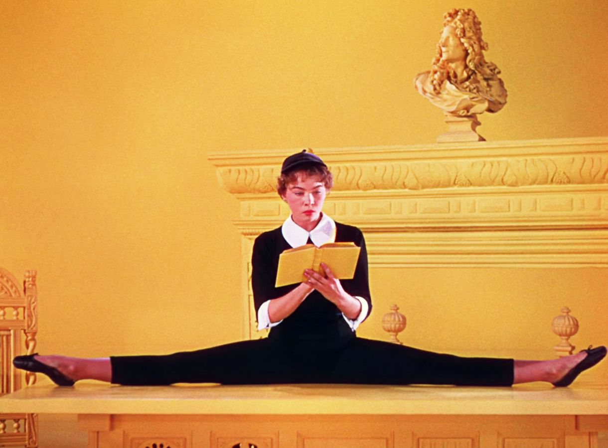 woman wearing beret doing splits while reading book