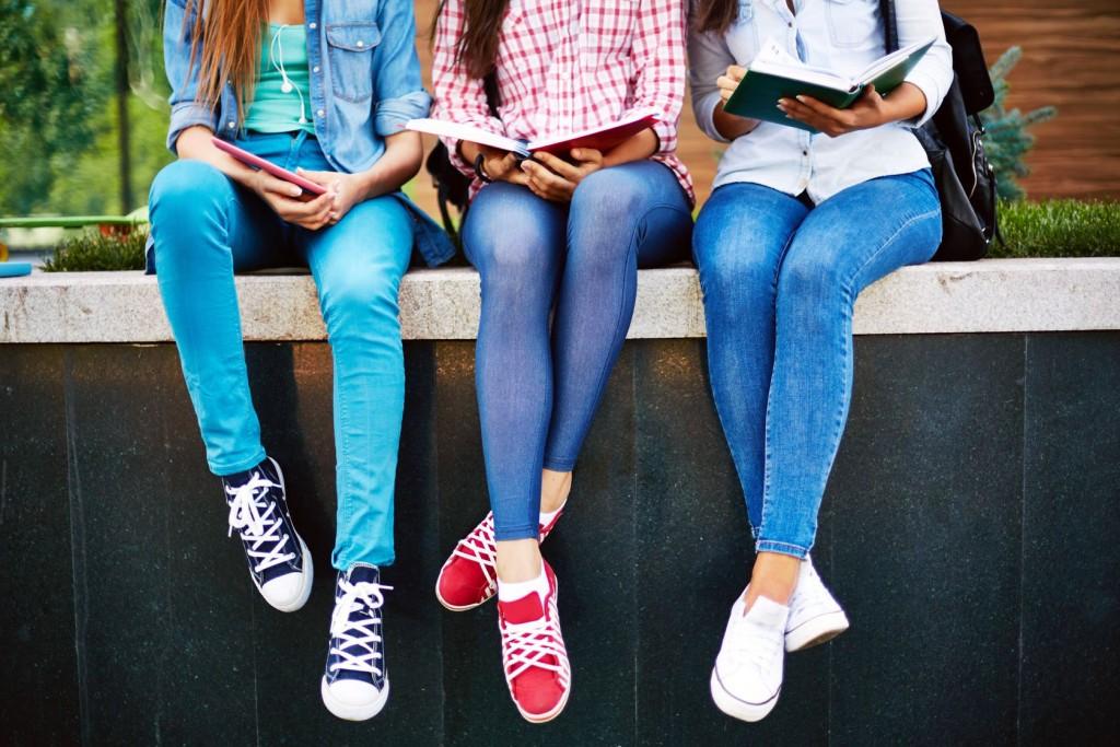 three teen girls reading outside