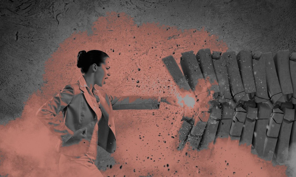 Image of businesswoman breaking bricks with hand-Edit