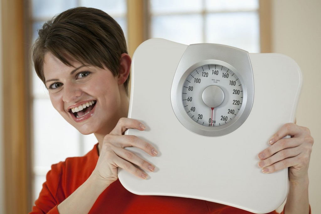 Attractive young woman holds a bathroom scale up while smiling at the camera. Horizontal shot