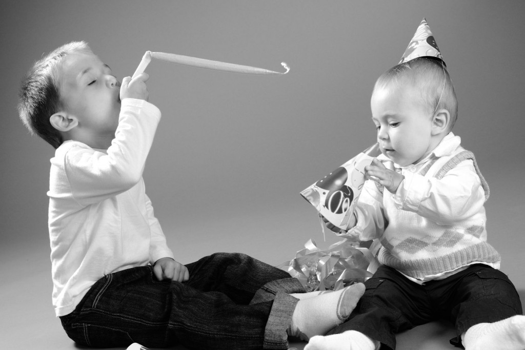 two small children playing with party favors