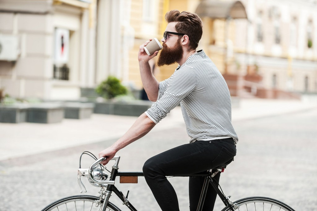 man drinking coffee on bike
