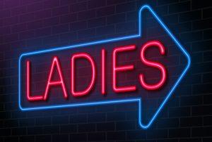 illuminated arrow sign depicting the word ladies