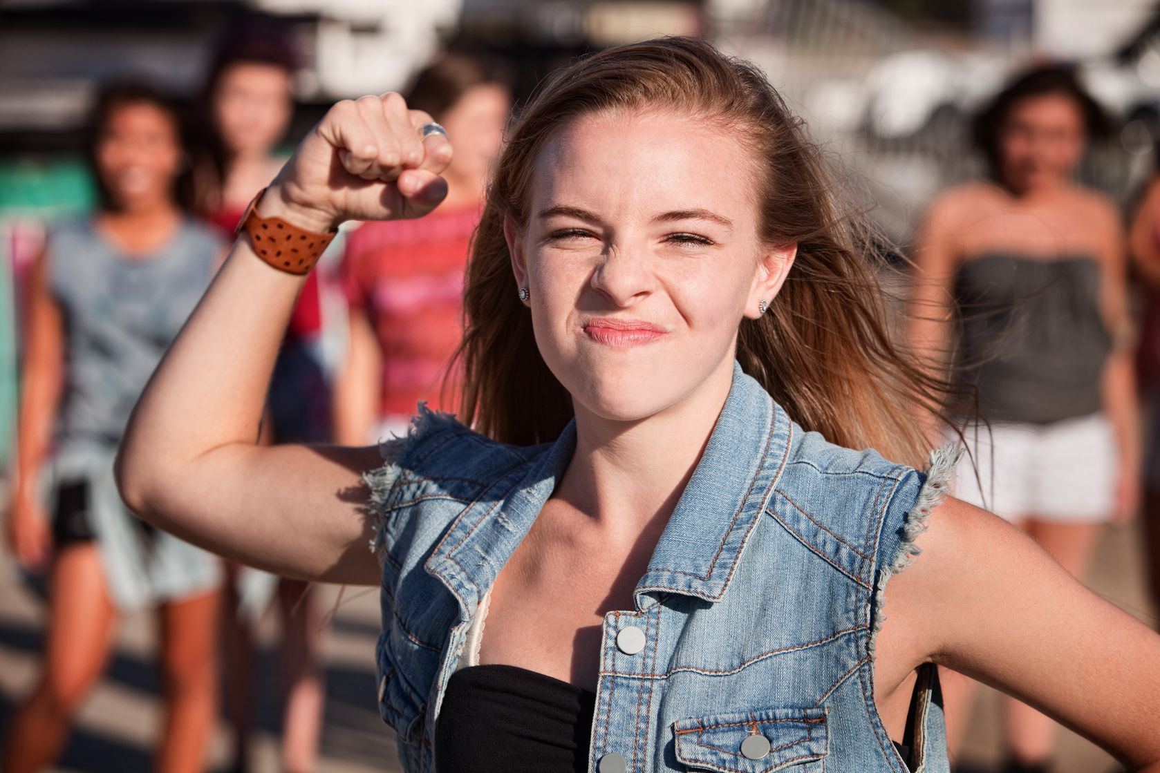 angry young girl in denim jacket raising fist