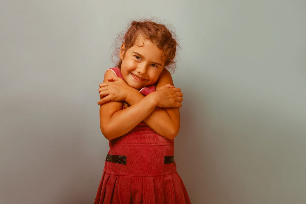 girl european appearance decade hugging herself on a blue  background retro