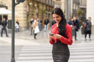 36582289 - portrait of hispanic bussinesswoman in urban background looking at her mobile phone