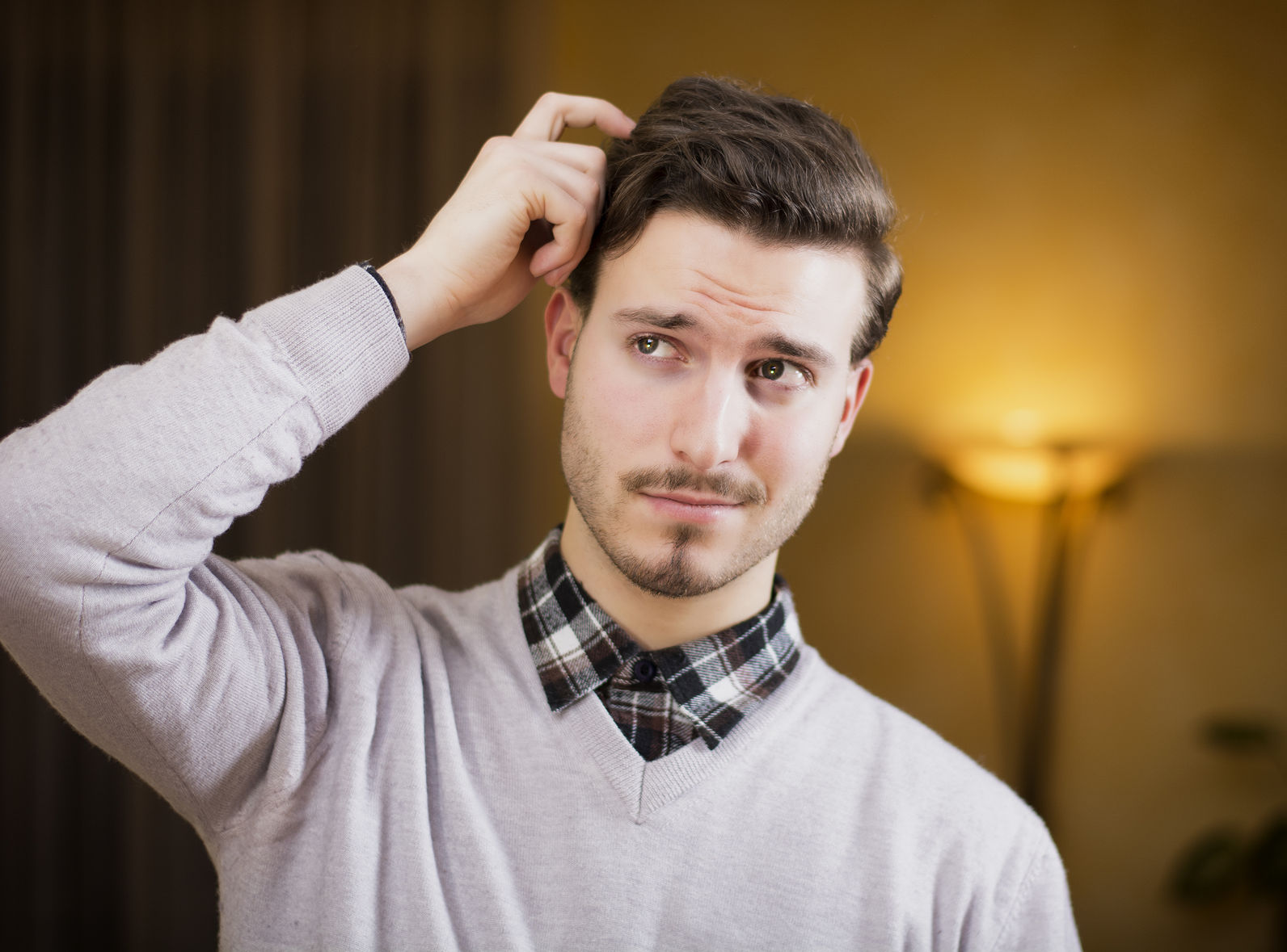 young man scratching his head in confusion