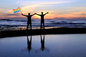 37337529 - silhouette of a gay couple holding a rainbow pride flag at sunset.