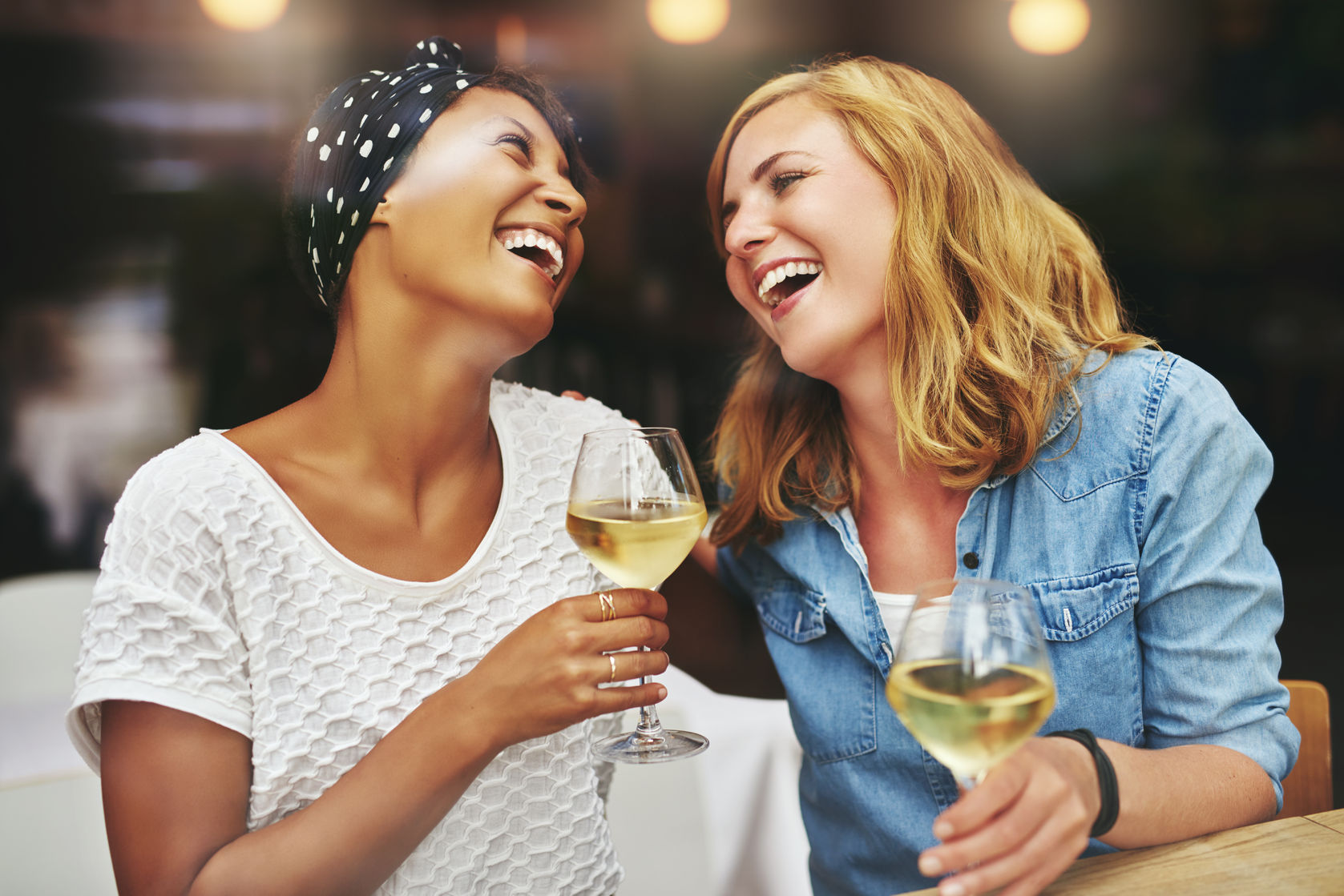 46626161 - two young attractive vivacious multiethnic female friends celebrating and laughing together over a glass of white wine