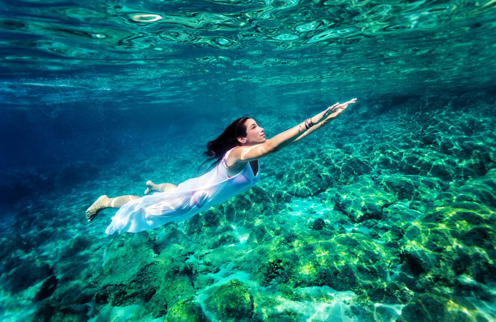 34015015 - refreshing swimming underwater, beautiful young woman wearing fashion white long dress and dive into clear transparent sea, luxury summer vacation concept