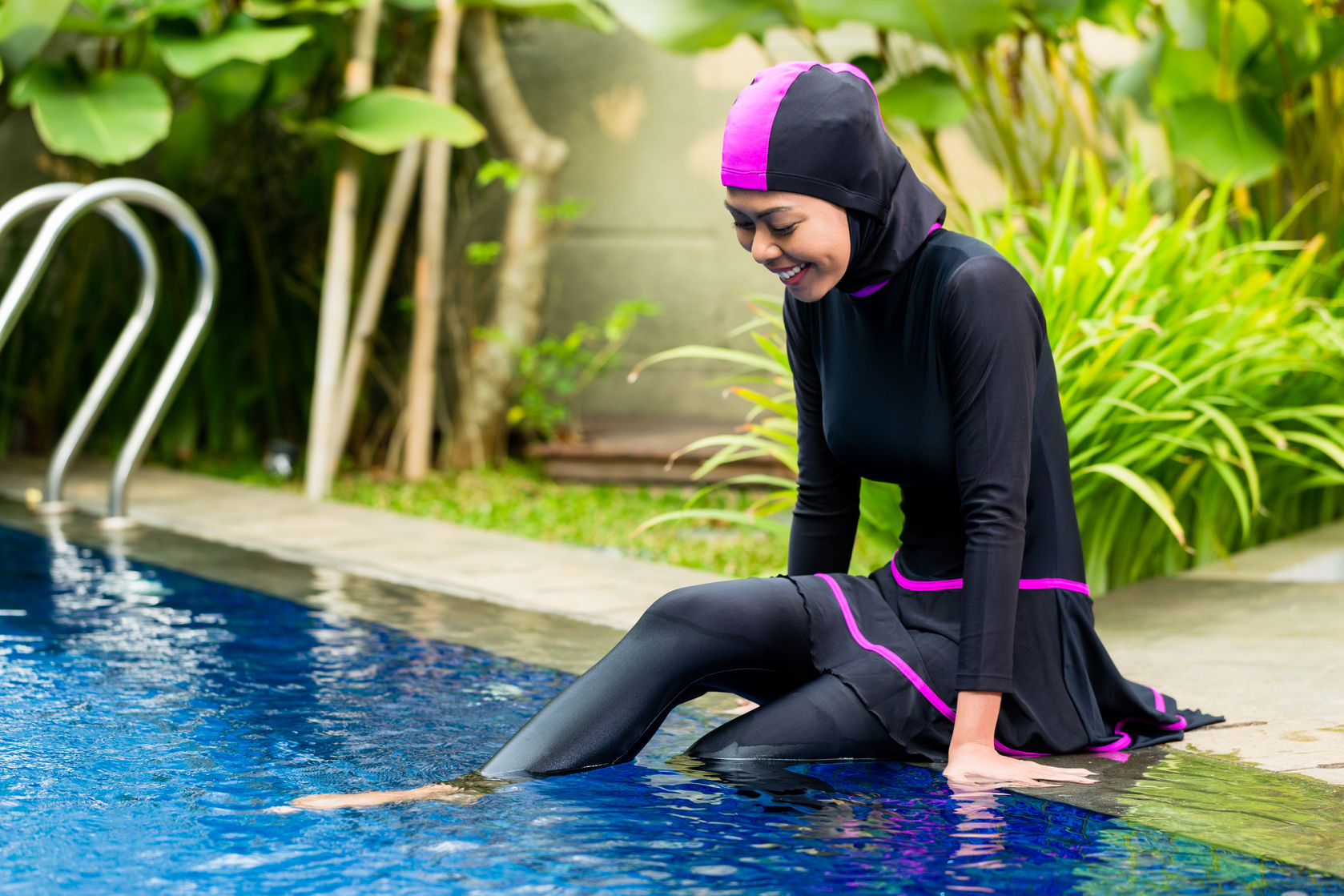 33765803 - muslim woman or girl sitting at pool in tropical garden wearing burkini halal swimwear