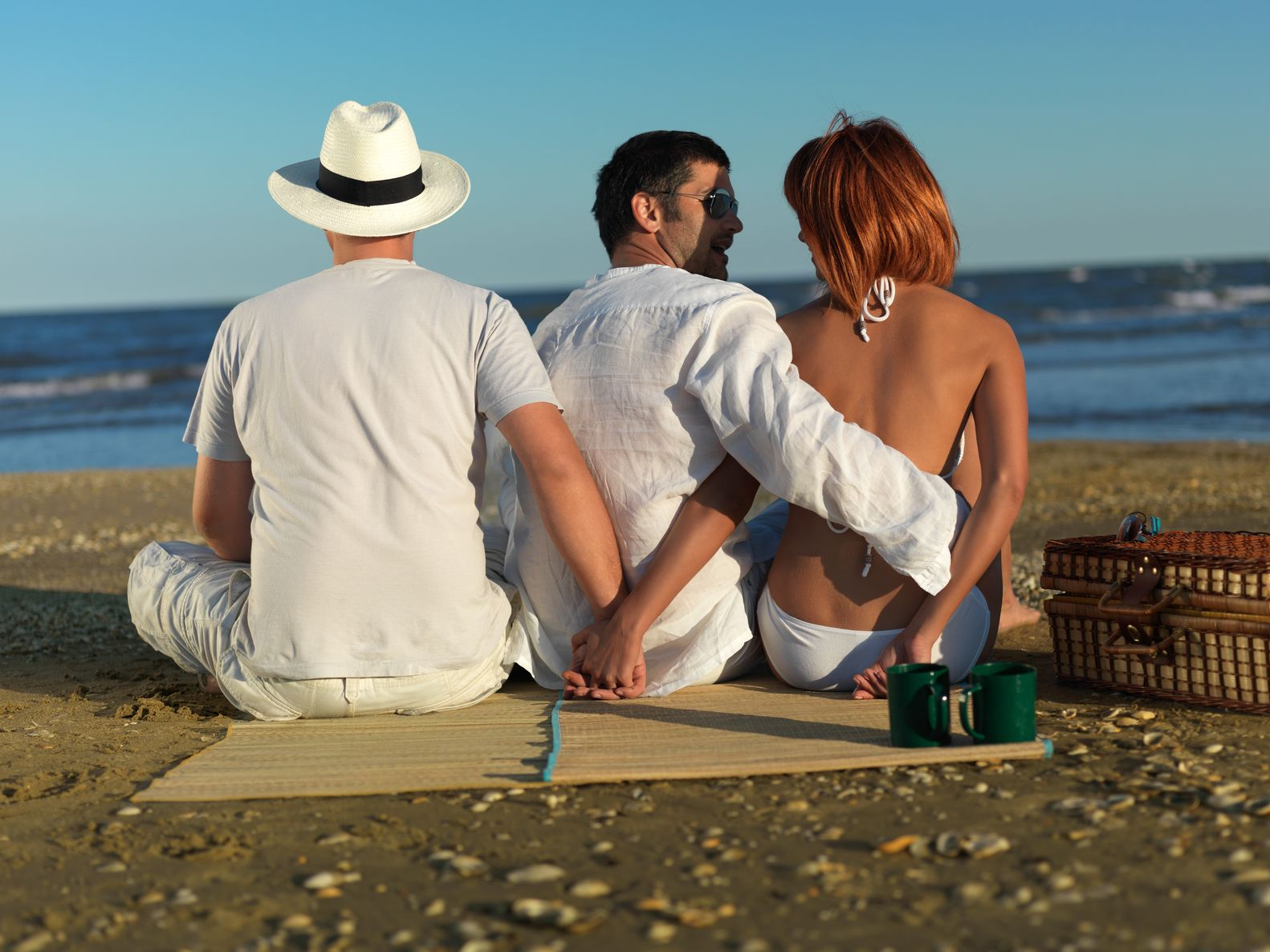 16038750 - young woman talking with the boyfriend, while holding hands with another man, at a picnic by the sea shore