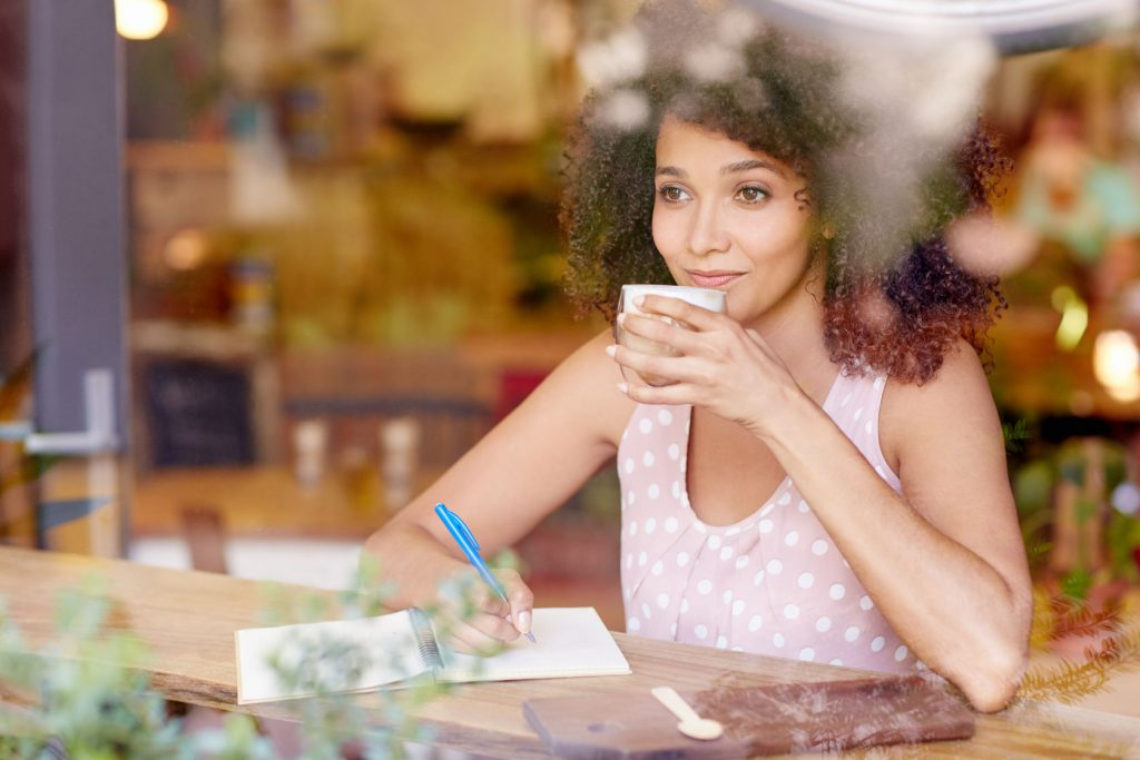 51356875 - beautiful mixed race woman sitting in a coffee shop sipping her latte and daydreaming while gazing out of the window