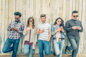 48007791 - young people looking down at cellular phone - teenagers leaning on a wall and texting with their smartphones - concepts about technology and global communication