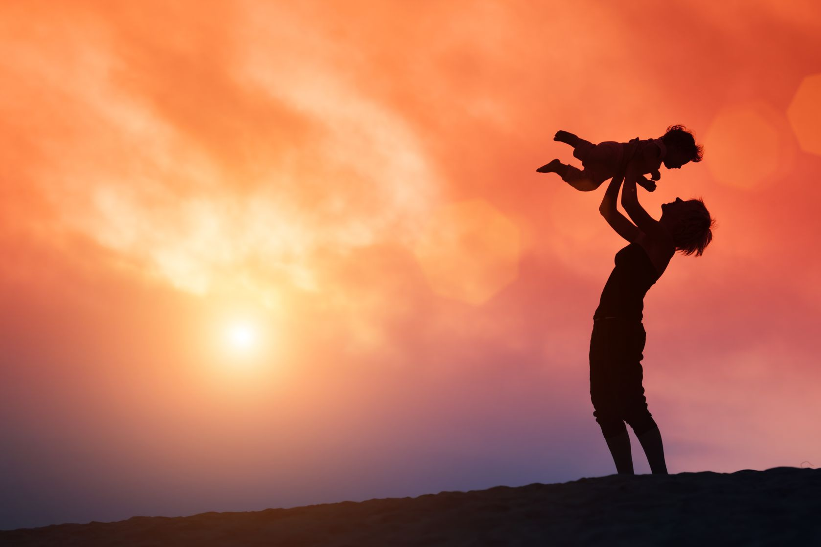 18709037 - mother lifting toddler child in air over scenic sunset sky