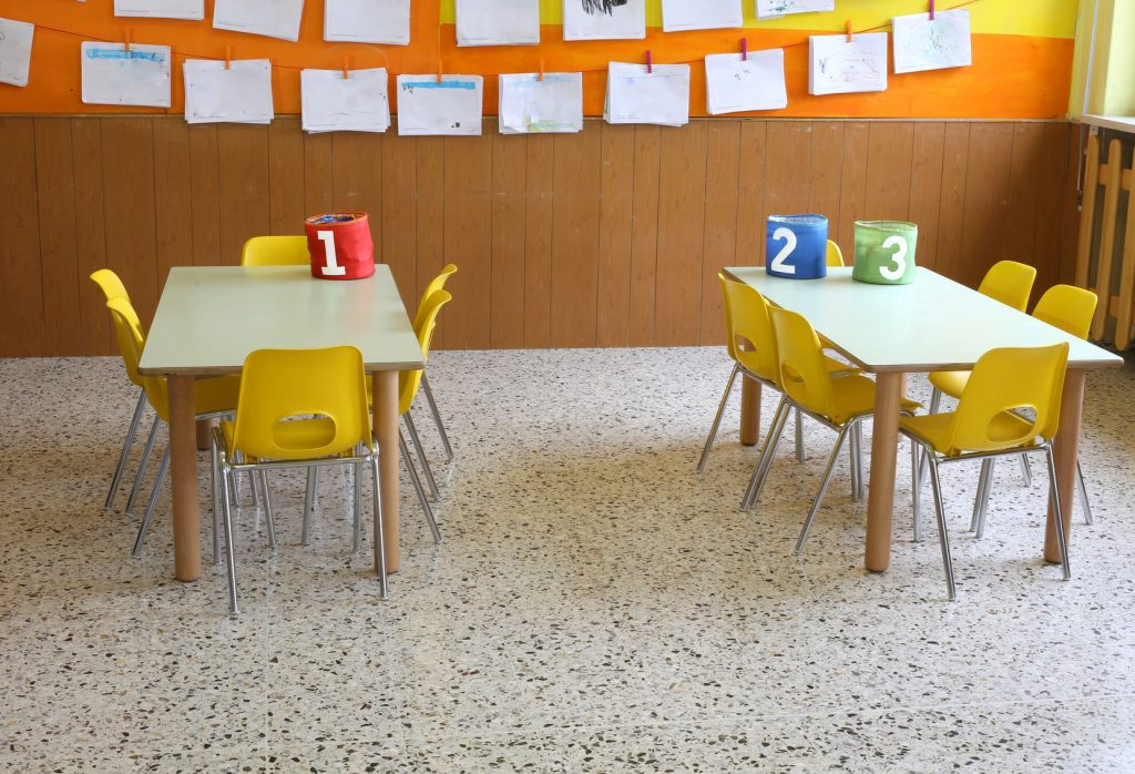 56045682 - kindergarten classroom with the yellow chairs and many children's drawings on the walls