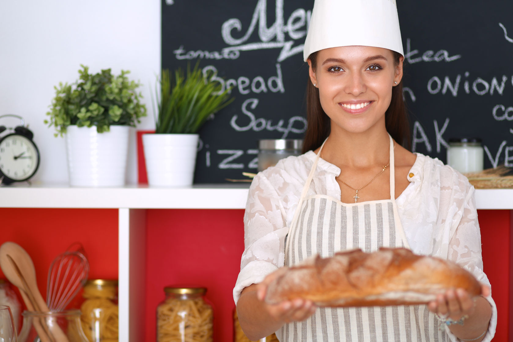 43777300 - young woman holding tasty fresh bread in her kitchen .