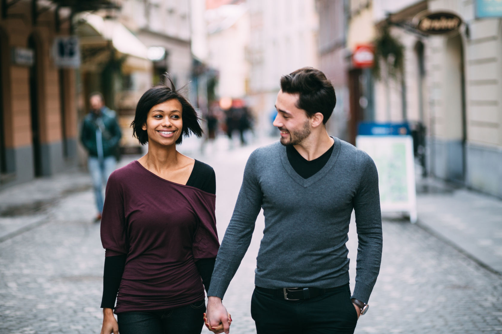36766213 - interracial couple holding hands on the street