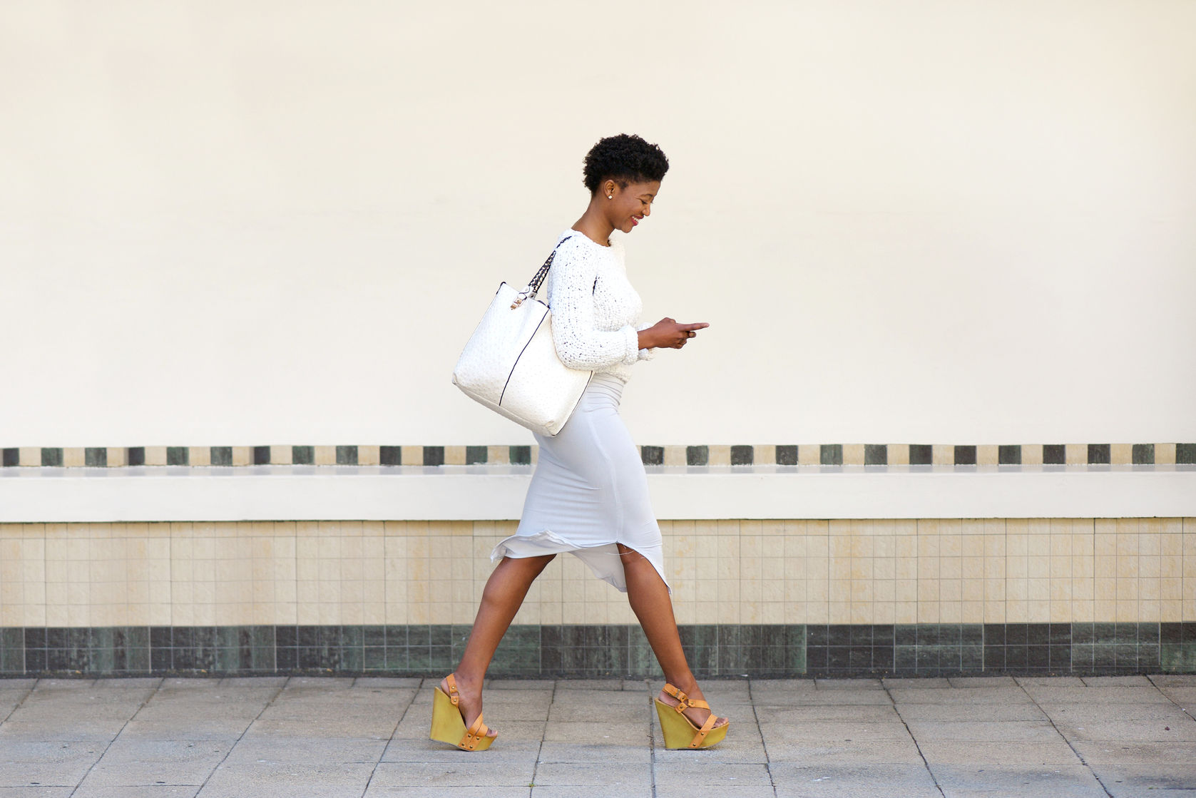 36328180 - full length side portrait of a young woman walking and sending text message on cell phone