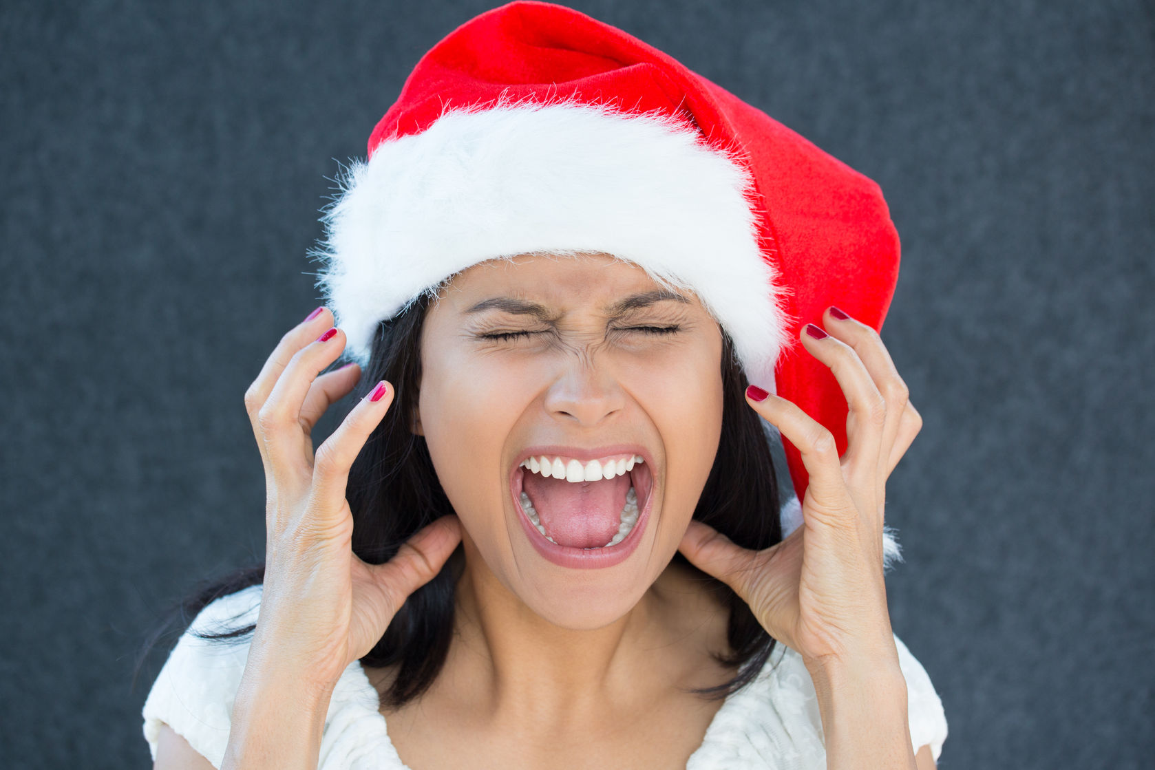 32215284 - closeup portrait of a cute christmas woman with a red santa claus hat, white dress, screaming out loud, frustrated, eyes shut in rage. negative human emotion on an isolated grey background.